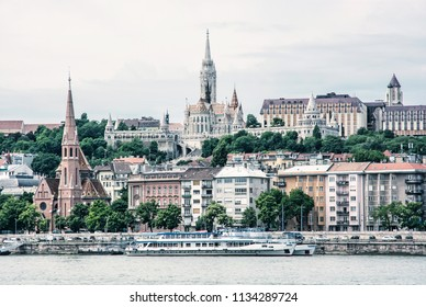 Matthias church, Fishermans bastion and Calvinist church in Budapest, Hungary. Cultural heritage. Architectural theme. Danube river bank with cruise ships. Blue photo filter.