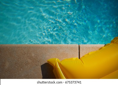The mattress and hat lie on the edge of the pool. top view