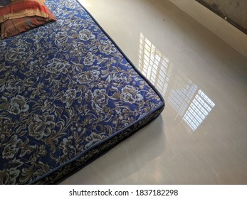 A mattress on floor where the tiles are relecting windows