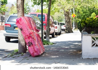 A mattress wrapped in plastic and discarded at the curbside