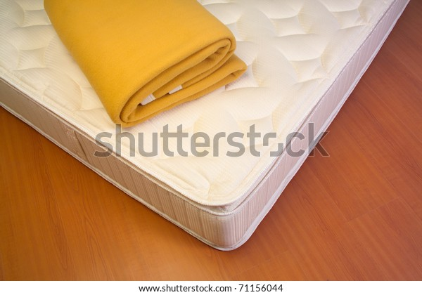 Mattress and yellow blanket