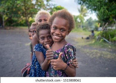 Matupit, East New Britain / Papua New Guinea - July 4, 2019: Group of kids portrait. Two girls smiles to the camera, while two boys hide behind them. Some of them have characteristic blonde hair