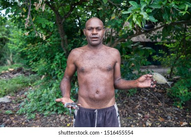 Matupit, East New Britain / Papua New Guinea - July 4, 2019: fisherman holding a small fish and a squid in his hands after pulling fishing nets in the sea shore, with jungle behind him