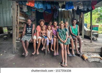 Matupit, East New Britain / Papua New Guinea - July 5, 2019: Tolai family with many children sitting in the porch of their wooden house in Matupit village