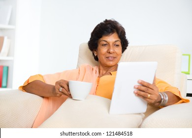 Mature 50s Indian woman drinking coffee / tea and using digital computer tablet at home