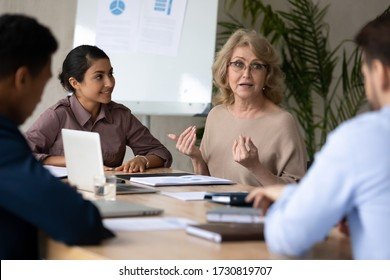 Mature 60 year old businesswoman with indian ethnic partner talking in boardroom at meeting. Confidence woman training diverse corporate team at briefing. Young employee share thoughts sitting.