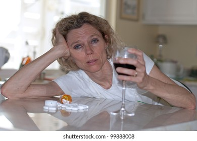 mature addicted woman drinking wine and pills