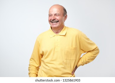 Mature adult man laughing looking at the camera over white background.