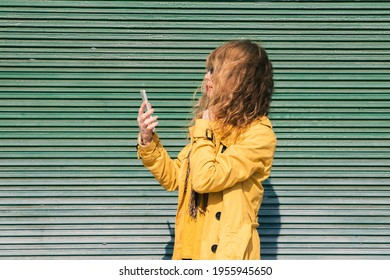 mature adult woman using smartphone on the street in front of the blind