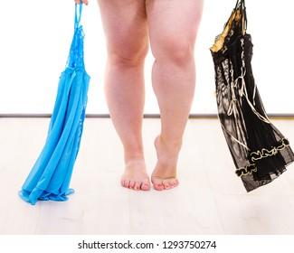 Mature adult woman wearing satin lingerie picking nightwear sleepwear. Plus size female feeling comfortable wearing sensual underwear.