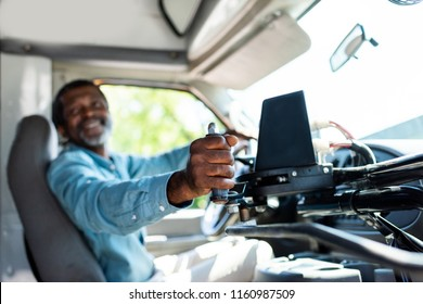 mature african american bus driver pulling lever at bus