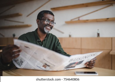 mature african american businessman with newspaper in cafe