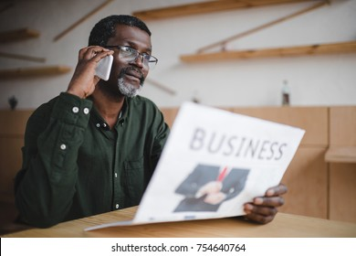 mature african american businessman talking by phone in cafe while reading newspaper