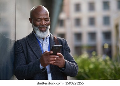 Mature african american businessman using smartphone in city texting on mobile phone