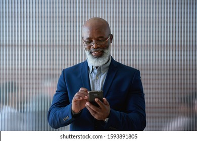Mature african american businessman using smartphone in office texting on mobile phone