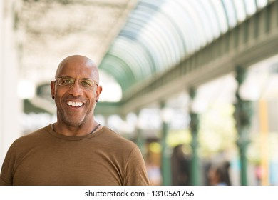Mature African American man smiling wearing glasses.