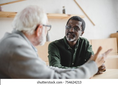 mature african american man talking to his friend at cafe