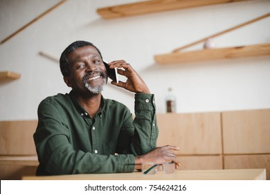 mature african american man talking by phone in cafe