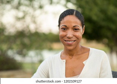 Mature African American woman smiling sitting outside.