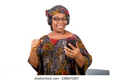 mature african woman in loincloth listening music using headphones and cellphone having hand gesture