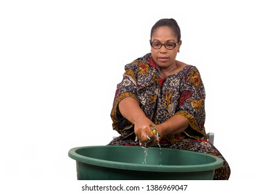 mature african woman in loincloth sitting doing laundry.