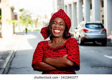 mature african woman standing outdoors head tied with a piece of loincloth watching the camera laughing.