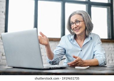 Mature aged business woman using a laptop for online video meeting with a colleagues. Senior teacher conducts classes, webinars. An elderly lady sits at the desk and talking at the online conference