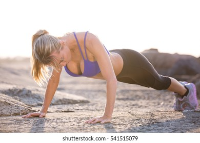 Mature aged woman does push ups by the seaside for exercise. She is wearing sports clothing. Sunset in the background. Woman is fit and healthy.
