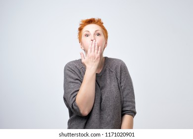 Mature amazed woman covering her mouth with hand on gray background. I wiil not tell this secret anybody. Conspiracy and mystery concept