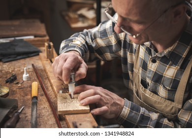 Mature artisan sitting at a rustic workbench while carefully applying glue on a small item