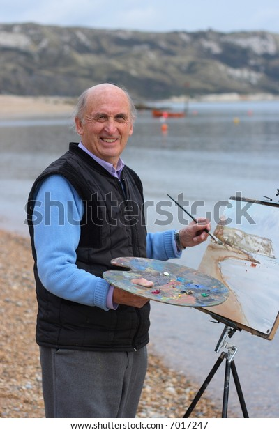 Mature artist painting a coastal landscape with paintbrush, easel and painter's palette.