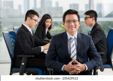 Mature Asian businessman on the background of his young colleagues having meeting