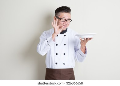 Mature Asian chef holding an empty plate, showing tasty and satisfied hand sign, standing on plain background.