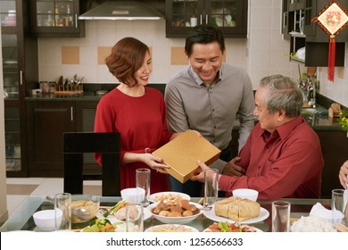Mature Asian couple giving present to senior man at Lunar New Year celebration, couplets with best wishes for coming year in the background