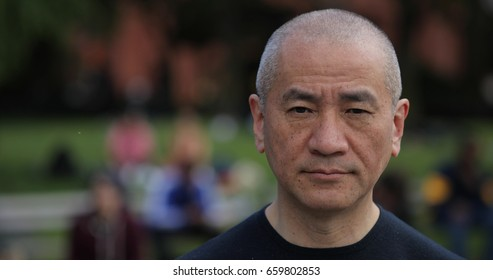 Mature Asian man in city park face portrait serious