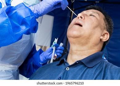 Homme asiatique mûr faisant un test de frottis nasal de la PCR 19 par nostril