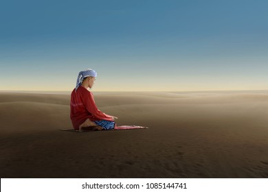 Mature asian man kneeling while pray to god with blue sky background