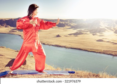 Mature asian woman doing kundalini or Zhan zhuang Qigong yoga. Spiritual energy, life force located at base of spine. Based on movement of internal energy, system of channels, energy centers, chakras