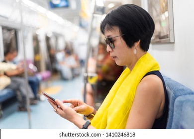 mature Asian woman using smartphone at the MRT carriage with copyspace