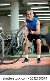 Mature athlete exercising with battle ropes on sports training in a gym.