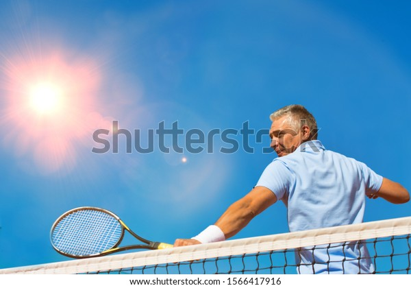 Mature athlete hitting the ball in tennis court with lens flare