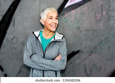 Mature Athletic Woman Relax After Running Against Gray Concrete Wall.