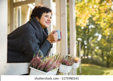 Mature attractive woman standing on Cozy wooden terrace with cup of hot coffee wrapped up in knitted warm sweater, happy smile. Lake house in autumn, yellow and red leaves on trees. Sunny day