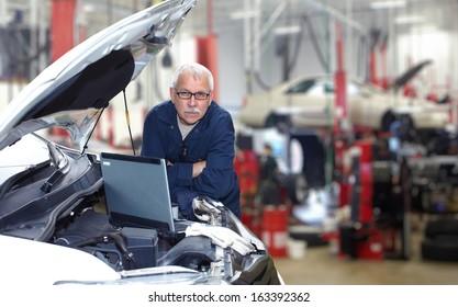 Mature auto mechanic working in car repair service.