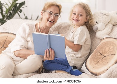 Mature babysitter reading a book to a small boy