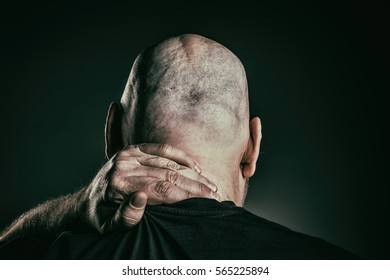 Mature bald man with neck pain, rear view of scalp
