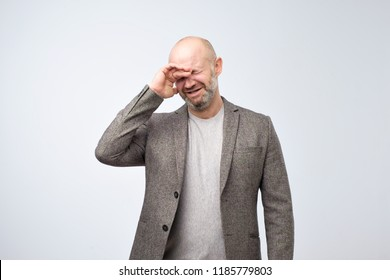 Mature bald man in suit with a problem is crying. Negative facial emotion
