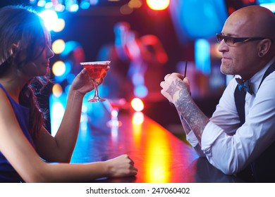Mature barman and young girl with drink talking in the bar