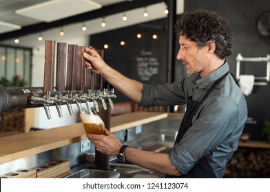 Mature bartender pouring beer in glass. Man pouring from tap fresh beer into the glass at pub. Side view of barman filling a glass with draught beer while standing at bar counter in restaurant.