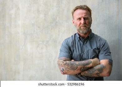 Mature bearded Caucasian man with hand tattoos